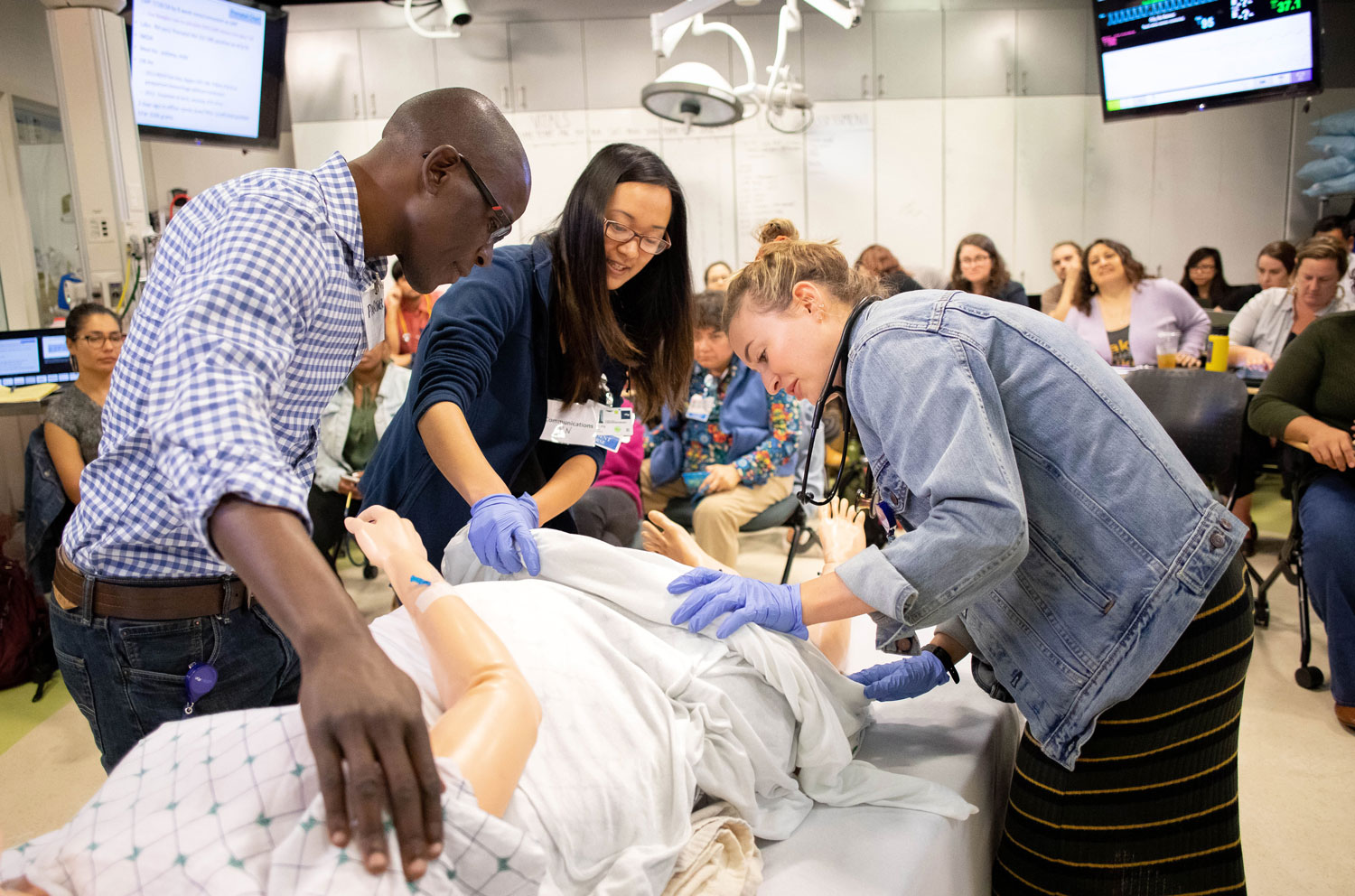 The UCSF School of Nursing's master's degree program and specialties were among the UCSF programs that placed highly in the latest U.S. News Best Grad School rankings. Nursing students, Emmanuel Onywera (left), Jennie Ling and Christina Camp (far right), learn how to care for an expectant mother using a simulation. Photo credit: Susan Merrell
