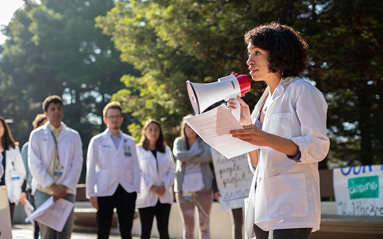 "Sheyda Aboii speaks to her fellow medical students, including, background left to right, Arun Burra, Andrés Calvillo and Avery Thompson and the community, at a White Coats for Black Lives (WC4BL) Teach-in, which set out to ""model an explicitly anti-racist healthcare education that elevates queer, disabled, formerly criminalized, and undocumented people of color in the communities and hospitals within which we work,"" on the 4th anniversary of WC4BL in 2018. Photo by Susan Merrell."