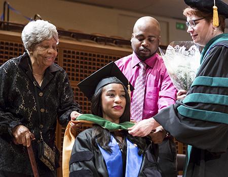 school of medicine graduate Jensara Clay at graduation ceremony with family members