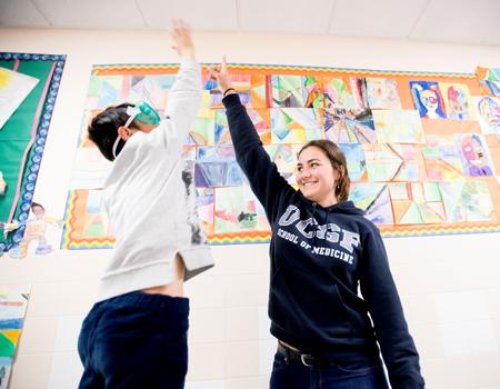fourth-grade student hi-fives a medical student