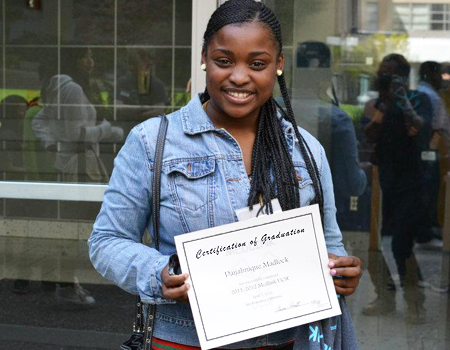 young African-American woman holding up graduation certificate
